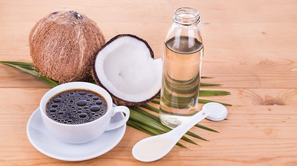 Bulletproof coffee with virgin coconut oil on wooden table