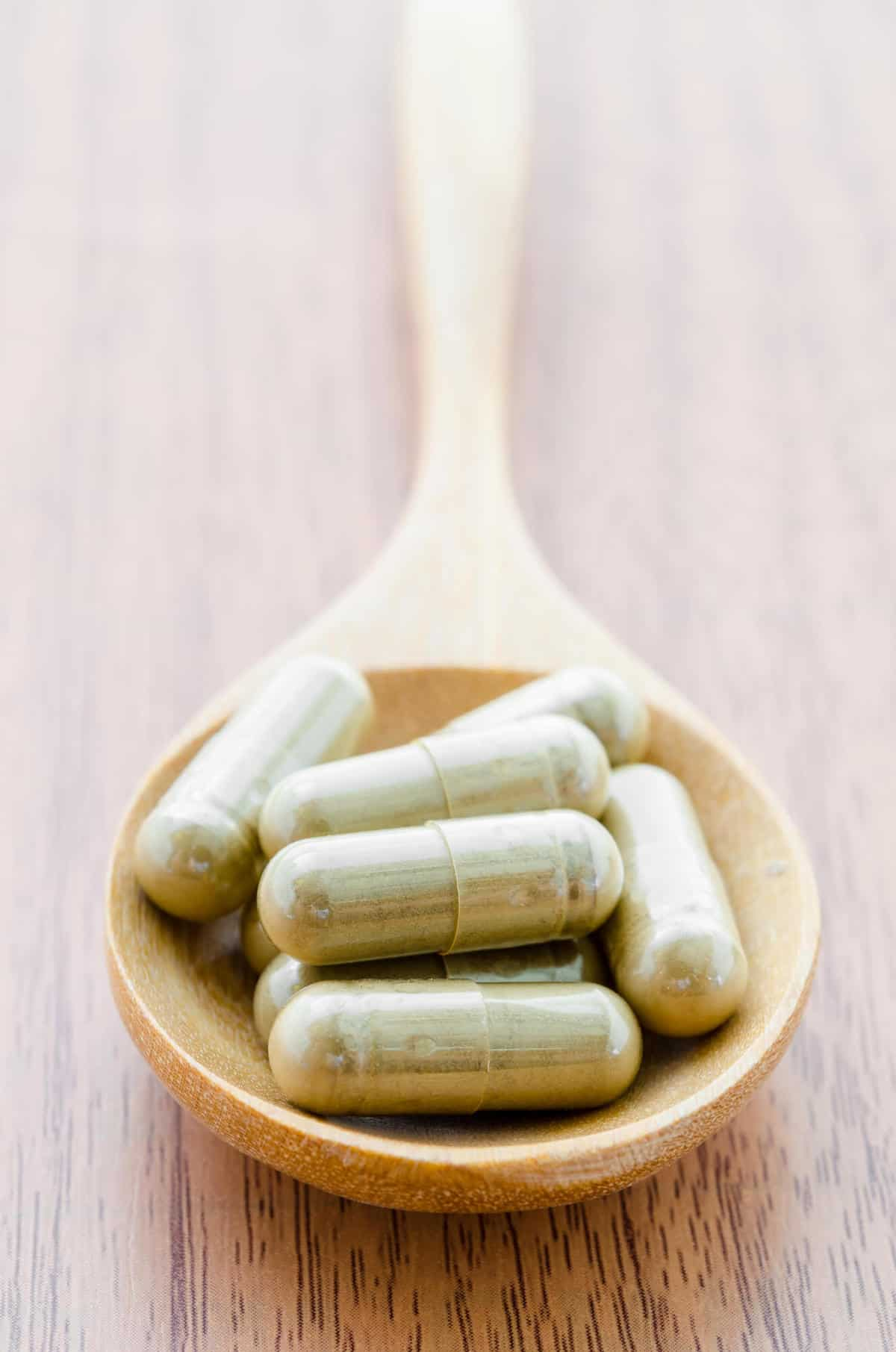 Supplement capsules on wooden spoon