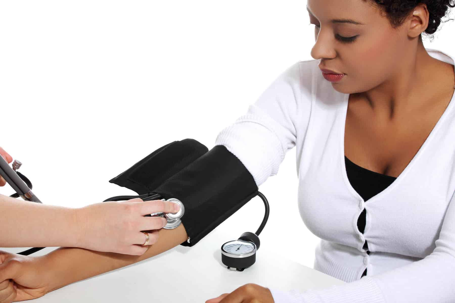 Doctor checking blood pressure of pregnant woman.